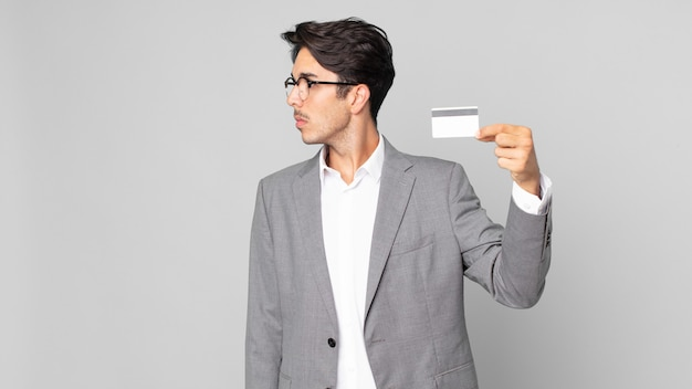 Jonge spaanse man op profielweergave denken, verbeelden of dagdromen en een creditcard vasthouden