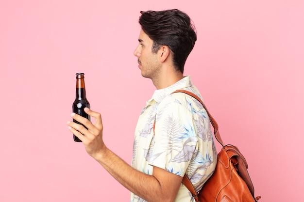 Jonge spaanse man op profielweergave denken, verbeelden of dagdromen en een flesje bier vasthouden