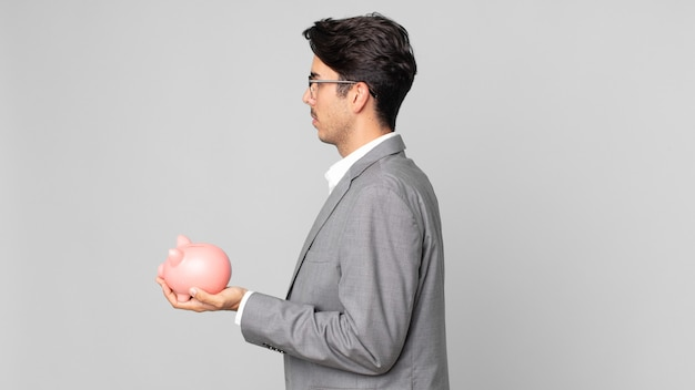Jonge spaanse man op profielweergave denken, verbeelden of dagdromen en een spaarvarken vasthouden