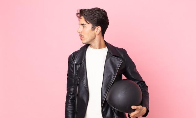 Jonge spaanse man op profielweergave denken, verbeelden of dagdromen. motorrijder concept