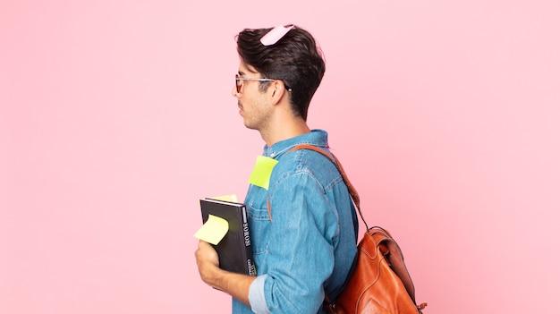 Jonge spaanse man op profielweergave denken, verbeelden of dagdromen. studentenconcept