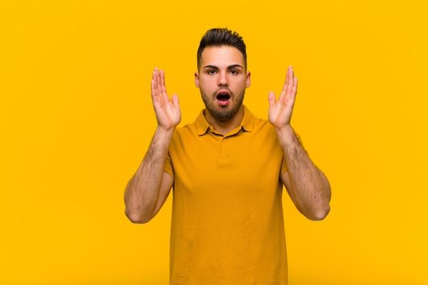 Jonge spaanse man op zoek geschokt en verbaasd, met verbaasde mond van verbazing bij het realiseren van iets ongelooflijk tegen oranje muur