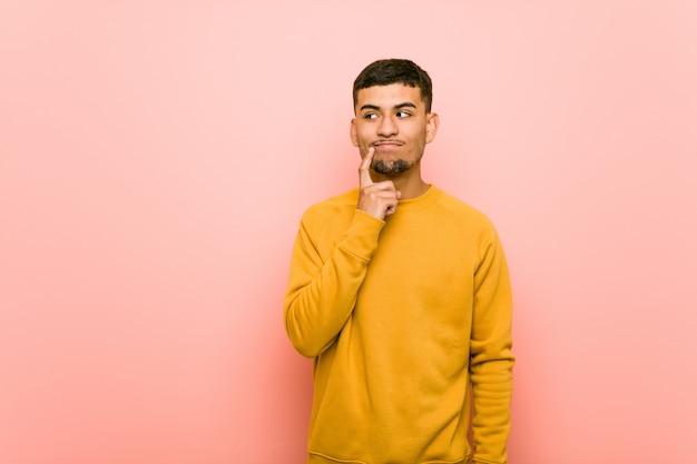 Jonge spaanse man opzij met twijfelachtige en sceptische uitdrukking