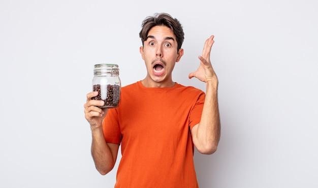 Jonge spaanse man schreeuwen met handen omhoog in de lucht. koffiebonen concept