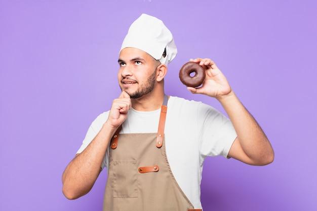 Jonge spaanse man twijfelende of onzekere uitdrukking. chef of bakker concept