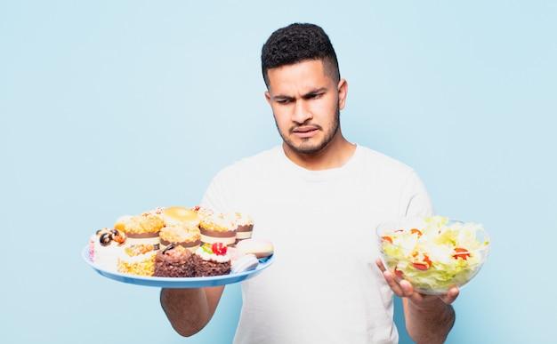 Jonge spaanse man twijfelende of onzekere uitdrukking en dieetconcept