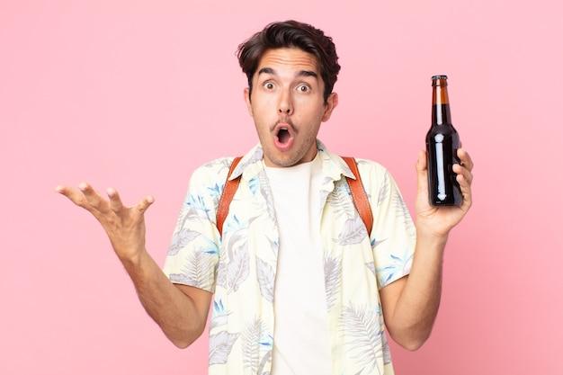 Jonge spaanse man verbaasd, geschokt en verbaasd met een ongelooflijke verrassing en met een flesje bier