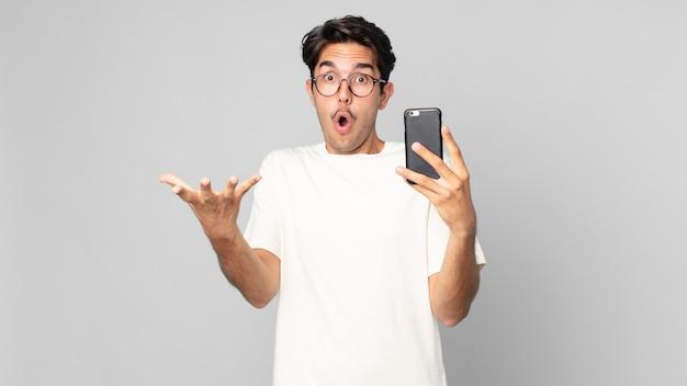 Jonge spaanse man verbaasd, geschokt en verbaasd met een ongelooflijke verrassing en met een smartphone