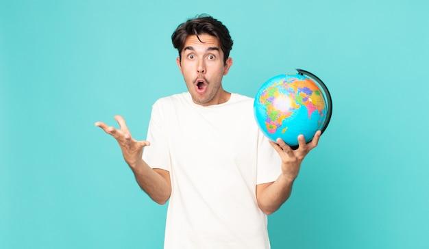 Jonge spaanse man verbaasd, geschokt en verbaasd met een ongelooflijke verrassing en met een wereldbolkaart