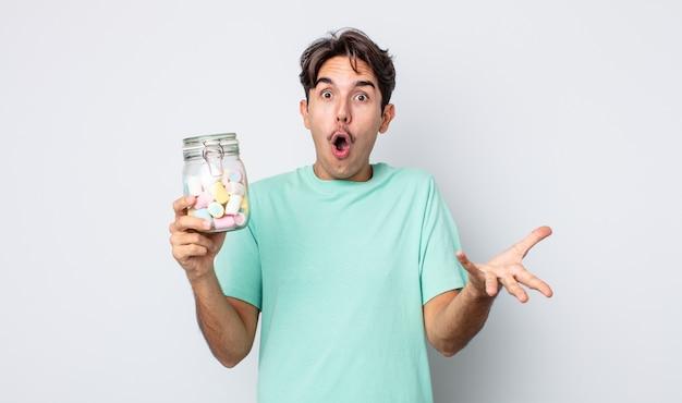 Jonge spaanse man verbaasd, geschokt en verbaasd met een ongelooflijke verrassing. gelei snoepjes concept