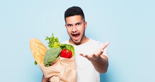 Jonge spaanse man verraste uitdrukking. winkelen groenten concept