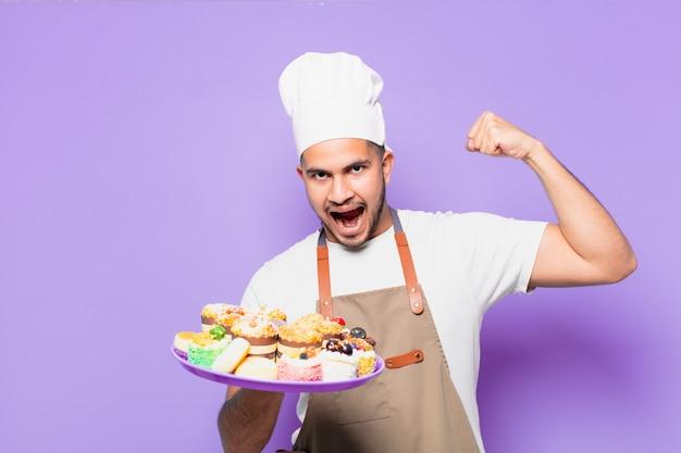 Jonge spaanse man viert succesvol een overwinning. bakker met cupcakes concept