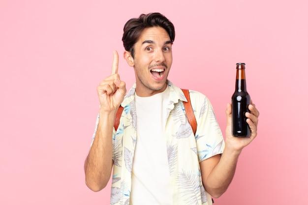 Jonge spaanse man voelt zich een gelukkig en opgewonden genie nadat hij een idee heeft gerealiseerd en een flesje bier vasthoudt