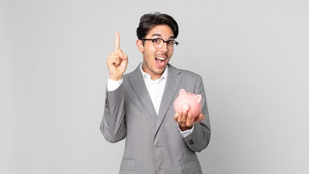 Jonge spaanse man voelt zich een gelukkig en opgewonden genie nadat hij een idee heeft gerealiseerd en een spaarvarken vasthoudt