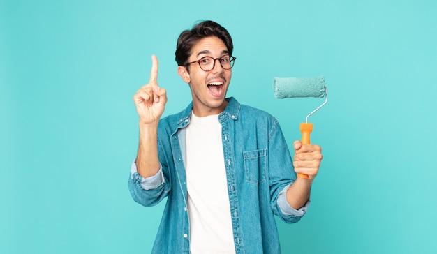 Jonge spaanse man voelt zich een gelukkig en opgewonden genie nadat hij een idee heeft gerealiseerd en een verfroller vasthoudt