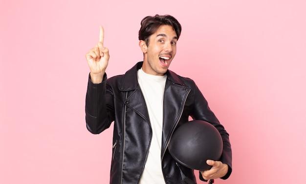 Jonge spaanse man voelt zich een gelukkig en opgewonden genie nadat hij een idee heeft gerealiseerd. motorrijder concept