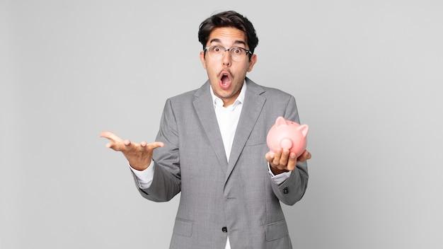 Jonge spaanse man voelt zich extreem geschokt en verrast en houdt een spaarvarken vast Premium Foto