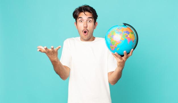 Jonge spaanse man voelt zich extreem geschokt en verrast en houdt een wereldbolkaart vast