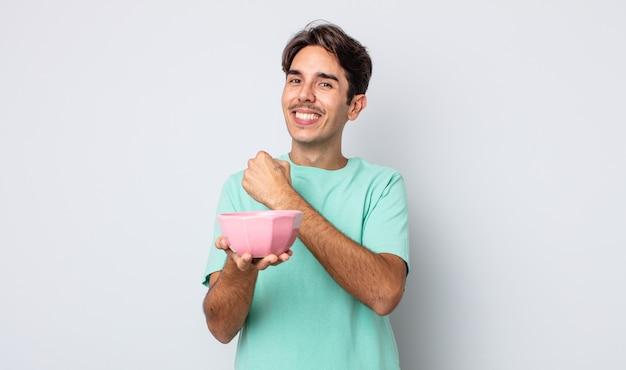 Jonge spaanse man voelt zich gelukkig en staat voor een uitdaging of feest. lege kom concept
