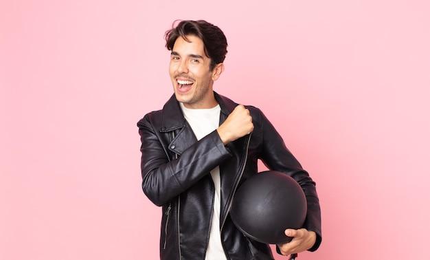 Jonge spaanse man voelt zich gelukkig en staat voor een uitdaging of feest. motorrijder concept