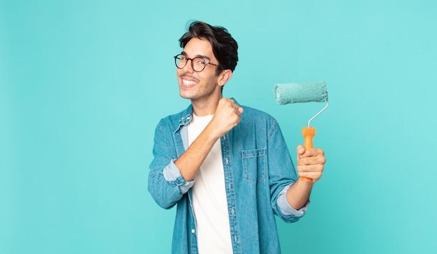 Jonge spaanse man voelt zich gelukkig en staat voor een uitdaging of viert en houdt een verfroller vast
