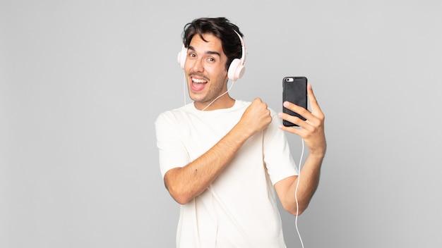Jonge spaanse man voelt zich gelukkig en staat voor een uitdaging of viert feest met koptelefoon en smartphone