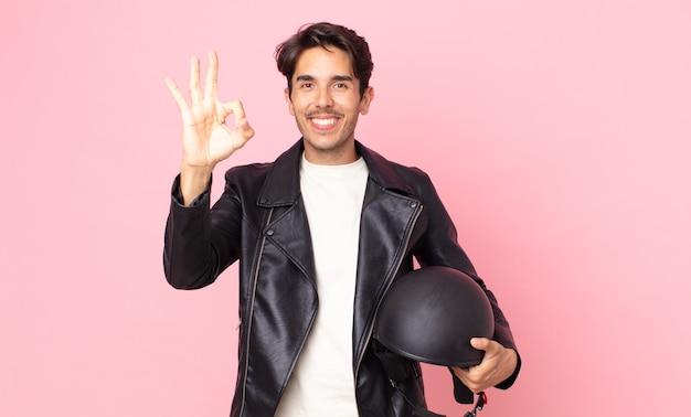 Jonge spaanse man voelt zich gelukkig en toont goedkeuring met een goed gebaar. motorrijder concept