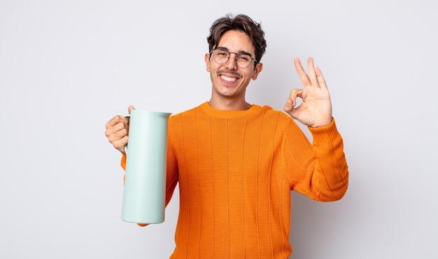 Jonge spaanse man voelt zich gelukkig en toont goedkeuring met een goed gebaar. thermos concept