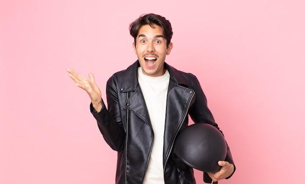 Jonge spaanse man voelt zich gelukkig en verbaasd over iets ongelooflijks. motorrijder concept