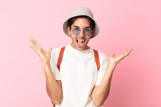 Jonge spaanse man voelt zich gelukkig en verbaasd over iets ongelooflijks. zomer concept