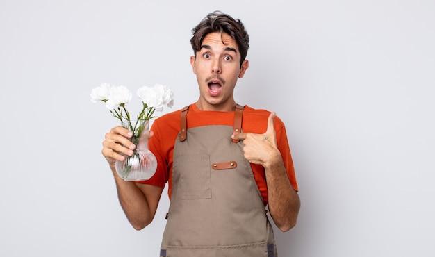 Jonge spaanse man voelt zich gelukkig en wijst naar zichzelf met een opgewonden. bloemist concept