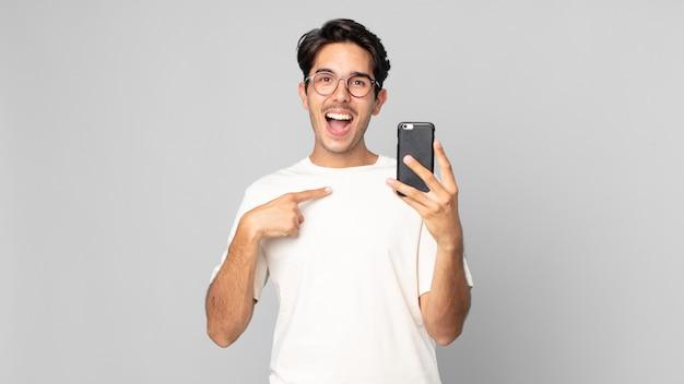 Jonge spaanse man voelt zich gelukkig en wijst naar zichzelf met een opgewonden en houdt een smartphone vast