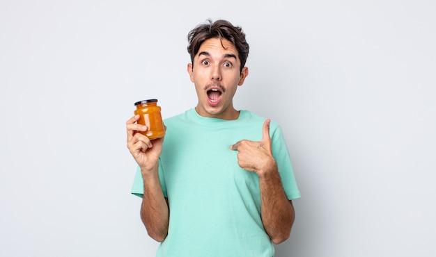 Jonge spaanse man voelt zich gelukkig en wijst naar zichzelf met een opgewonden. perzik gelei concept