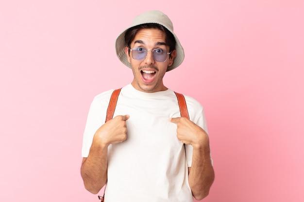 Jonge spaanse man voelt zich gelukkig en wijst naar zichzelf met een opgewonden zomer concept