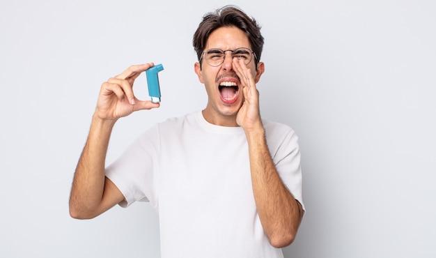 Jonge spaanse man voelt zich gelukkig, geeft een grote schreeuw met de handen naast de mond. astma concept