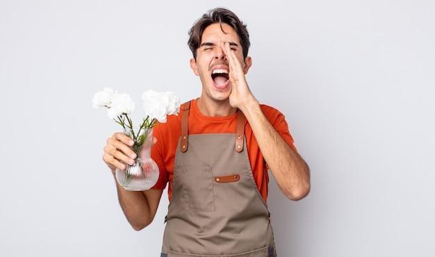 Jonge spaanse man voelt zich gelukkig, geeft een grote schreeuw met de handen naast de mond. bloemist concept