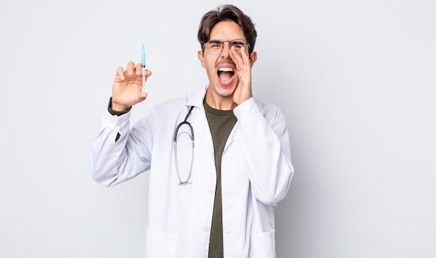 Jonge spaanse man voelt zich gelukkig, geeft een grote schreeuw met de handen naast de mond. dokter spuit concept