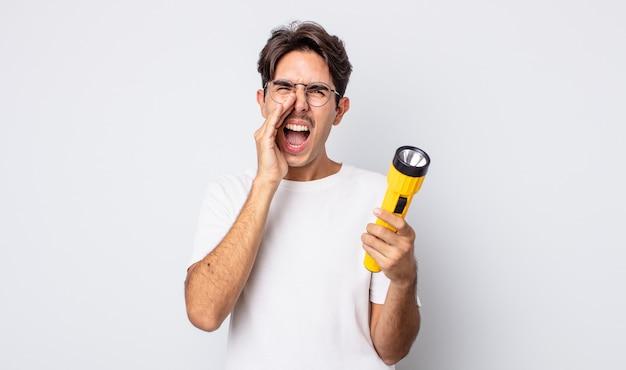 Jonge spaanse man voelt zich gelukkig, geeft een grote schreeuw met de handen naast de mond. lantaarn concept