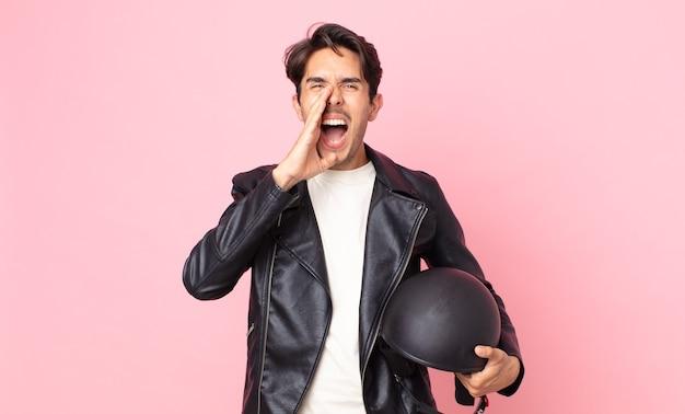 Jonge spaanse man voelt zich gelukkig, geeft een grote schreeuw met de handen naast de mond. motorrijder concept