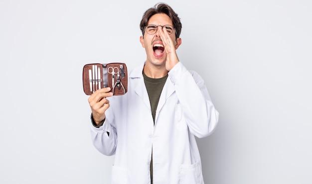Jonge spaanse man voelt zich gelukkig, geeft een grote schreeuw met de handen naast de mond. podoloog nagels tools