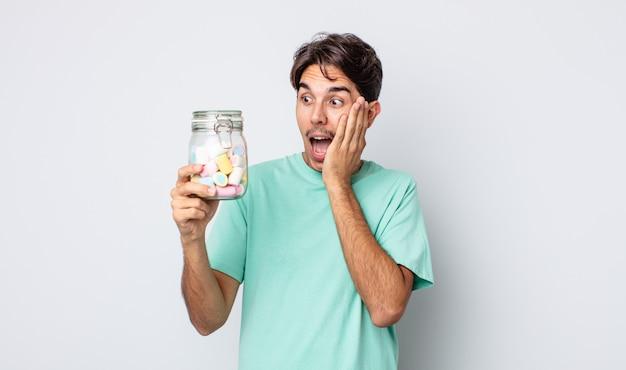 Jonge spaanse man voelt zich gelukkig, opgewonden en verrast. gelei snoepjes concept