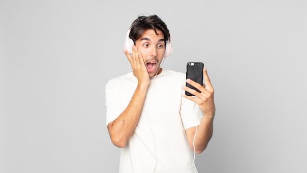 Jonge spaanse man voelt zich gelukkig, opgewonden en verrast met koptelefoon en smartphone
