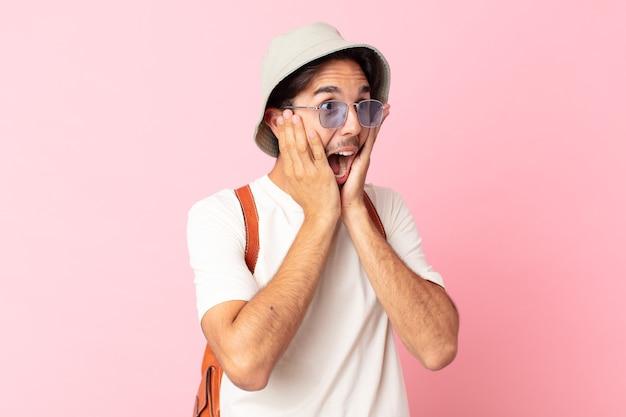 Jonge spaanse man voelt zich gelukkig, opgewonden en verrast. zomer concept