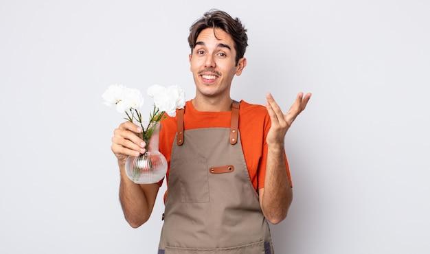 Jonge spaanse man voelt zich gelukkig, verrast door het realiseren van een oplossing of idee. bloemist concept