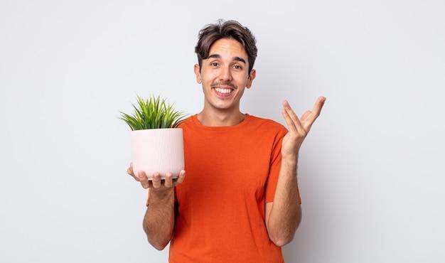 Jonge spaanse man voelt zich gelukkig, verrast door het realiseren van een oplossing of idee. decoratief plantenconcept