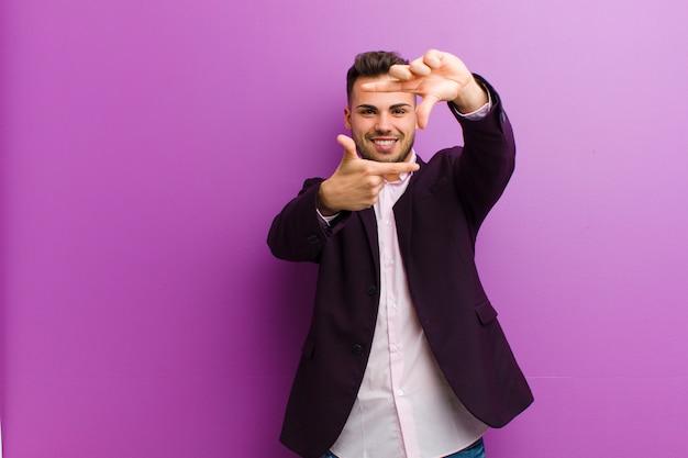 Jonge spaanse man voelt zich gelukkig, vriendelijk en positief, lacht en maakt een portret of fotolijst met handen