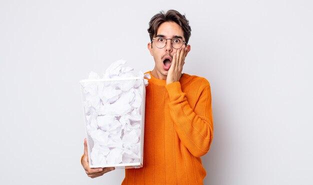 Jonge spaanse man voelt zich geschokt en bang. papier ballen prullenbak concept