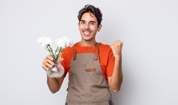 Jonge spaanse man voelt zich geschokt, lacht en viert succes. bloemist concept