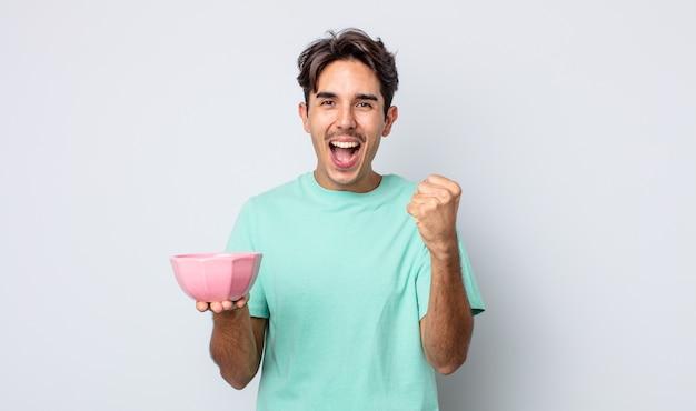 Jonge spaanse man voelt zich geschokt, lacht en viert succes. lege kom concept