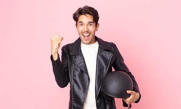 Jonge spaanse man voelt zich geschokt, lacht en viert succes. motorrijder concept